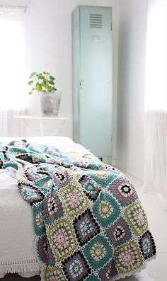 Sweet cottage bedroom with turquoise locker for storage and pretty afghan throw to add color for bed.  Colors include: Turquoise, Purple, White, Pink, and Yellow.