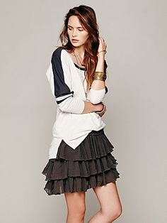 Flouncy washed chiffon mini skirt with tiered ruffles. Srunch ruffle detailing at waist. Stretchy smocking at back of waist for easy fit and wear. Asymmetrical hemline.