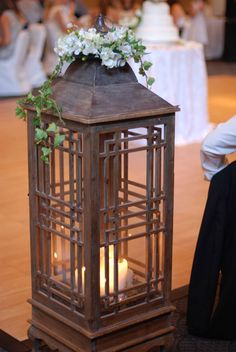 lanterns with candles and flowers on each end of the head table