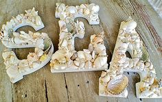 sea shell covered letters with bucket of old sea shells