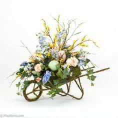 Custom spring silk arrangement placed in a moss wheelbarrow