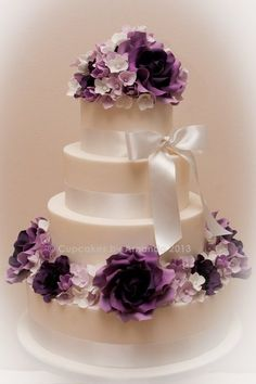 I want the top of my wedding cake to be a bunch of shades of purple flowers like this with a picture cake topper and a green bow!!