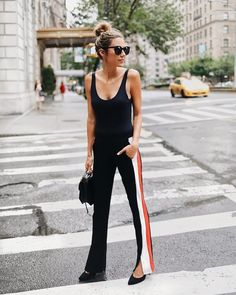 Casual cool #streetstyle. All black outfit with stripe detail on the black pants. Pointy two heels and messy bun.