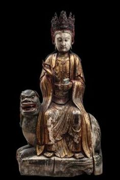A magnificent large wood figure of Manjusri seated on a lion China, Yuan dynasty, 14th century h. cm. 128  Manjusri (Wenshu in Chinese), the bodhisattva of wisdom, is usually portrayed sitting on the back of the lion, as seen in this extraordinary sculpture. It often appears together with Samantabhadra (Puxian in Chinese), who in turn is riding an elephant.  In this statue the divinity is portrayed with his right hand raised in the vitarkamudrā position