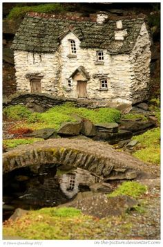 Fairy-sized old stone cottage, replete with stacked stone garden wall and an arched stone bridge over a little creek.