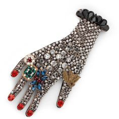 A brooch in metal with hand motif encrusted with glass and resin beads. The intricately detailed design is finished with ring, bracelet and fingernail details. <ul> <li>Metal with aged gold finish</li> <li>Vintage rose glass and resin beads</li> <li>Right hand</li> <li>Made in Italy</li> <li>Gucci guarantees, internally and within its supply chain, respect for standards of Social & Environmental Responsibility in
