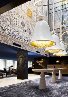 Lobby - large fixtures over standing height tables - Andaz Amsterdam Hotel designed by Marcel Wanders