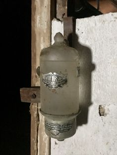 """Circa 1910. Found in the attic, glass """"fire grenades"""" as they were called could be picked up out of their holder and tossed onto a fire. Some were on mounts that were heat reactive and placed over boilers. Very early units were filled with salt water, but older one are filled with CTC, a chemical later used as a weapon in World War One."""