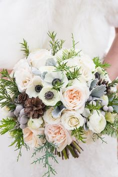 winter wedding bouquets white bouquet with cones and spruce branches calgary wedding photographer via instagram