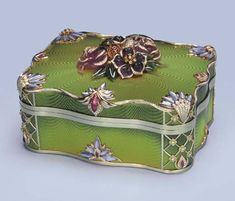 A GOLD, ENAMEL AND GEM-SET BOX Of rectangular scalloped form, the green guilloché enamel with central floral and foliate cluster of coloured quartz and jade with diamond detail to the dyed mother-of-pearl and diamond borders, 20.2 cm. long, with London hallmark for 18 carat gold <3<3<3