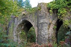 "Scotland, Dunans Castle - Dunans Bridge, designed by Thomas Telford. Built in 1815 to commemorate the battle of Waterloo. The three-arched rubble construction is considered internationally important as it is the only extant bridge of this type. Now listed as ""At Risk""."