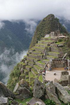 Machu Picchu es el nombre que se le da a un antiguo poblado Inca, construido a mediados del siglo XV, esta ubicado sobre una elevación rocosa unida entre las montañas Huayna Picchu y Machu Picchu, en Perú, al oriente de la Cordillera central, a unos 130 kilómetros de Cuzco, la cual es la ciudad importante mas cercana.