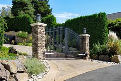 Beautiful outward swinging, double swing gate set between two stone pillars with…