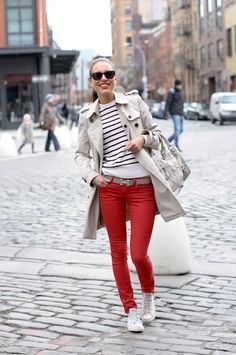 still wearing last year's staples: sneakers, red jeans, stripes, trench coat
