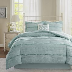 Create a shabby chic look in your bedroom with the Madison Park Isabella Collection. This solid blue comforter has ruffles and quilting paired with a contrasting embroidered decorative pillow for a clean update for your space.