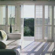 Bi-fold plantation shutters add privacy and light control to floor-to-ceiling windows and sliding glass doors.