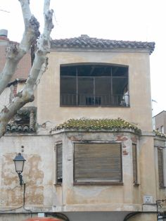 Detalle . Cesped apoderándose del colorido tajado de una casa abandonada del casco histórico