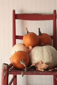 Pile of pumpkins on old red chair by Sandra Cunningham