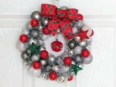 Just a perfect touch for your holiday decorations. This 10 - inch wreath is loaded with sparkly red, silver and white shatterproof ornament balls. Silver tinsel garland is wrapped thorughout the wreath. Pretty glass stars of red and green are scattered around the wreath.  A red polka dotted bow tops the piece with a cute spiral red velvet ornament with a bell inside, comes down the center of the wreath.