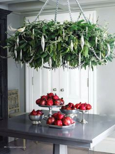 Pointed oblong ornaments hung in a green, suspended wreath, over a pomegranate display - perfect