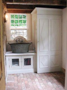 Galvanized tub sink with hidden washer-dryer and storage.