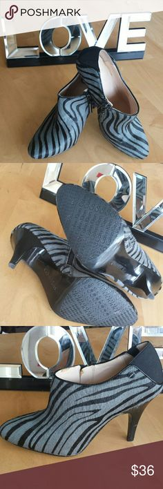 """Calvin Klein Black/Gray Zebra Striped Ankle Boots Calvin Klein Jordan Black & Gray Zebra Striped Ankle Booties. Zebra striped calf hair. Zippered side. Barely warn. One small scratch on heel as shown in photo. Silver logo Calvin Klein stud detail. Size 6M. 3.5"""" heel. These booties just ooze style!  Buy now before they get scooped up for fall!   . Calvin Klein Shoes Ankle Boots & Booties"""