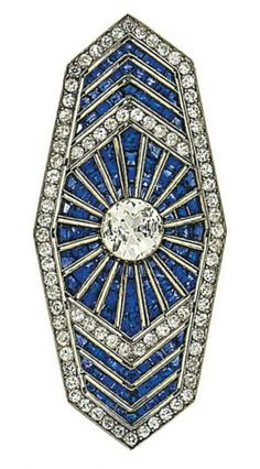 An Art Deco diamond and sapphire brooch, by Polak Aine. Of elongated hexagonal panel design, the central old brilliant-cut diamond collet to a calibré-cut sapphire multi ray surround with old-cut diamond and calibré sapphire chevron detail, within an old-cut diamond surround, 5.9cm long, French marks, circa 1935. Signed Polak Aine and numbered.