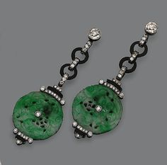 PAIR OF ART DECO JADE, ONYX AND DIAMOND EARRINGS, CIRCA 1925 Designed as fringes of diamond-set links and onyx rings supporting 2 carved and pierced jade discs, the whole set with 56 old European-cut diamonds weighing approximately 1.35 carats and 2 rose-cut diamonds, mounted in platinum.