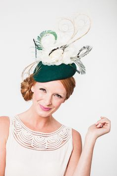 A racing green classic felt beret adorned with a stunning ivory silk rose and finished with fabulously colourful and ornate curled peacock swords. A beautifully feminine and elegant design. Featur…
