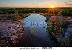 Stock Photo: Sunset scene with a small pond on the hilltop on a beautiful summer evening in Finland.  -