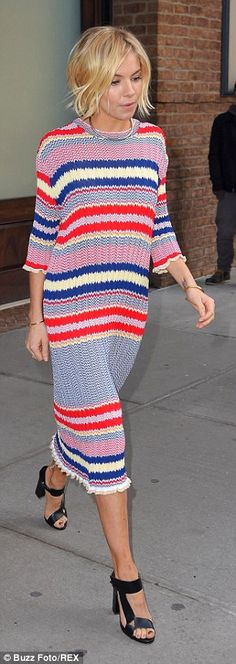 Strutting it: Sienna covered up her slender physique with multi-coloured striped dress whi...