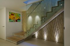 Textured wall behind the contemporary staircase with glass railing