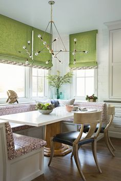 A breakfast nook is enlivened by green roman shades and a custom patterned cushion | archdigest.com