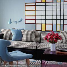 Farb- und Mustermix total! Das stilvolle Wohnzimmer mit schwarz-weißer Couch wird durch farbige Akzente in blau, rot und gelb aufgepeppt. Mehr farbige Wohnzimmer auf www.roomido.com/wohnideen/wohnzimmer/farben