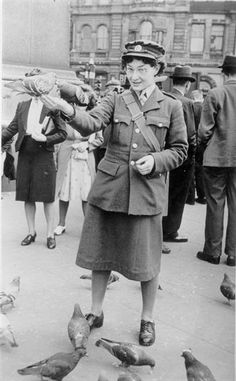 A member of the Auxiliary Territorial Service (ATS), Esther Ogg, in Trafalgar Square, London, feeding the pigeons. The ATS was the women's branch of the British Army in WW2.
