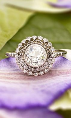 This truly exceptional vintage-inspired ring encircles a bezel set diamond with lavishly detailed latticework and a halo of shimmering diamonds.