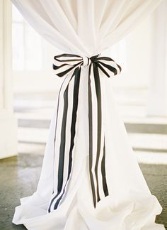 I like this idea for our future cabana. You can change out the ribbon for a different feel but not have to spend a lot on the curtains! - black + white striped bow detail