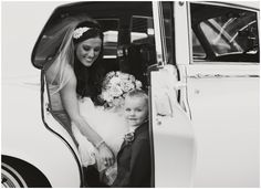 Timeless black and white wedding portrait of the bride and her son in an antique Rolls Royce at Blithewold Mansion in Bristol, RI photographed by Massart Photography, a Rhode Island newborn, family and wedding photographer.  www.massartphotography.com