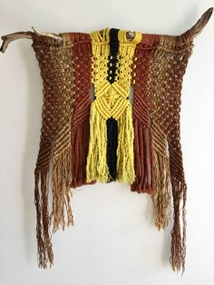 70s Vintage Hand Woven Wall Hanging - woven on an authentic tree branch - made of rope in the colors yellow, black, Burgundy, natural jute, and brown - unique shape and design  Measures: Wood piece is 32.5 wide 40 at the longest at the sides  CONDITION REFERENCE CHART RATING: Excellent Loses fibers when you move it due to age. Back side has grey dust marks. Both issues not a problem when hanging. Beautiful piece on the wall.  Thanks for looking and check out my other listings at…