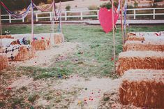 Whimsical carnival seating made out of haystacks and blankets or quilts #carnival #wedding