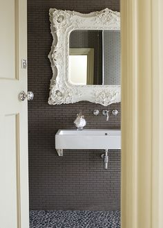 This beautiful Baroque white mirror is all this small bathroom needs to give it charm! Walls: Mirrors