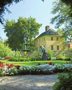 Behind an interpreter in one of Strawbery Banke's many historic gardens is an 1814–16 house that once belonged to Daniel Webster.