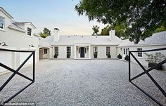 Grandiose: The entrance to the mansion shows black gates set against a white paved drive