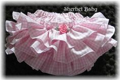 3 rows of very full gathered and edged ruffles. This is a full panty/diaper cover with elastic cased waist and elastic leg openings. The rolled edge on leg openings creates another sweet ruffle. All seams, ruffle edges and hems are serged with a pretty rolled edge