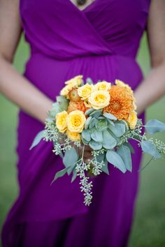 Orange spray roses, dahlias, succulent, and eucalyptus posey for bridesmaids.