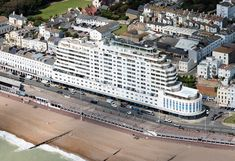 Inspired by the RMS Queen Mary, completed in it was the tallest block of flats in the UK - Marine Court in Hastings - East Sussex UK aerial image Hastings East Sussex, Aerial Images, Art Deco Buildings, Seaside Resort, Queen Mary, Countryside, England, Poster Ideas, Airports