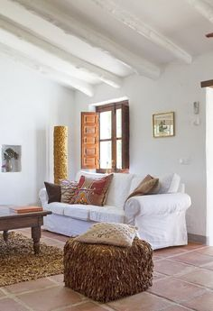 i am in love with the shaggy leather ottoman and the tile floor...look at the window shutters
