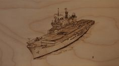 """This pyrography artwork is HMS Illustrious. Drawn here in her helicopter assault carrier version, I have drawn her on a piece of beech-faced plywood. This artwork is approximately 200 x 360mm (8"""" x14""""), and is unframed."""