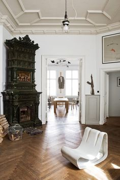German fashion designer Frank Leder's combined home and studio. Modern furnishing, white walls, tiled stove, herringbone wood flooring.