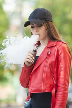 A woman wearing a black cap and a red jacket vapes tastefully Vape Pictures, Smoke Pictures, Sexy Women, Badass Women, Women Smoking, Girl Smoking, Alan Walker, Girl Photo Poses, Girl Photos